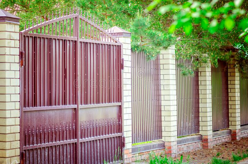 Modern metal gates and a fence with brick columns royalty free stock photos