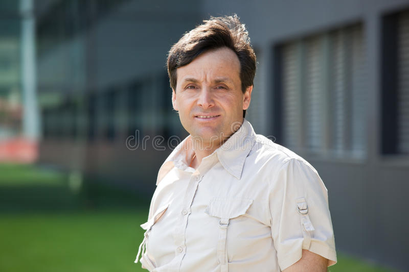 Modern middle-aged man. Portrait of a modern middle-aged man with a building on the background royalty free stock photo