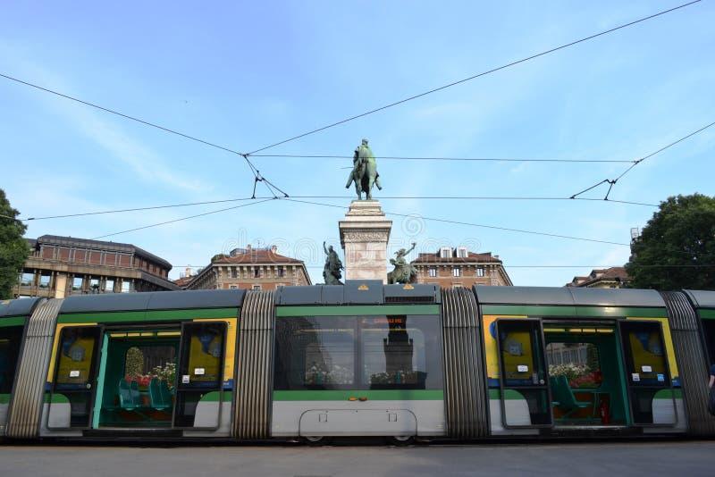 Modern Milan spårvagn som parkeras i den Cairoli fyrkanten med monumentet till Giuseppe Garibaldi royaltyfri bild
