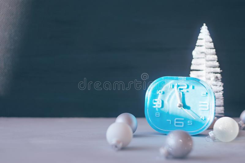 Modern minimal Christmas festive gift winter background. Close up blue clock, white Christmas tree, silver ornament ball on black royalty free stock image