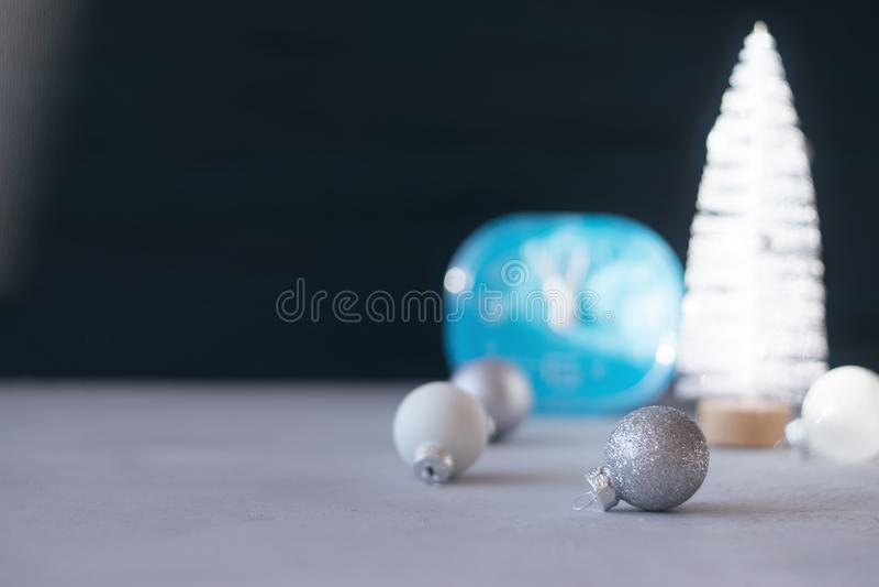 Modern minimal Christmas festive gift winter background. Close up blue clock, white Christmas tree, silver ornament ball on black royalty free stock photo