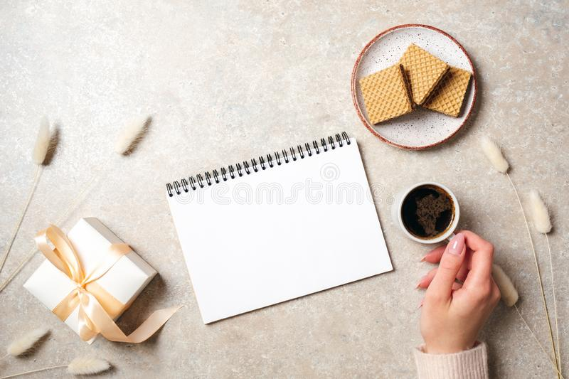 Modern minimal home workspace desk with blank paper notebook, human hand holding coffee cup, waffles, dry flowers on concrete stock image