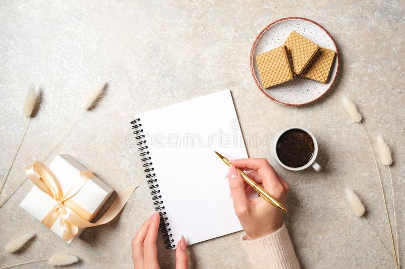 Modern minimal home workspace desk with human hand writing text message on blank paper notebook, waffles, dry flowers on concrete stock photos