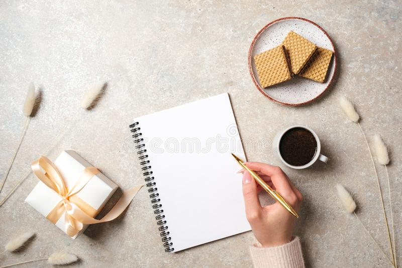 Modern minimal home workspace desk with human hand writing text message on blank paper notebook, waffles, dry flowers on concrete stock photography