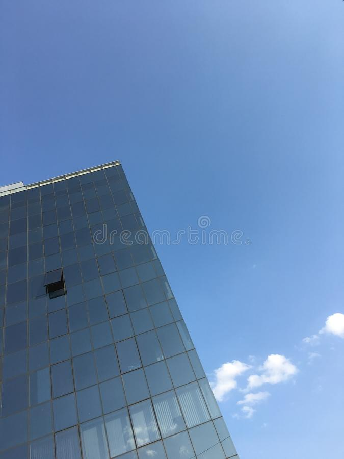Modern minimalist architecture. Tall office building glass windows against clear blue sky business texture background. Metaphor royalty free stock photo