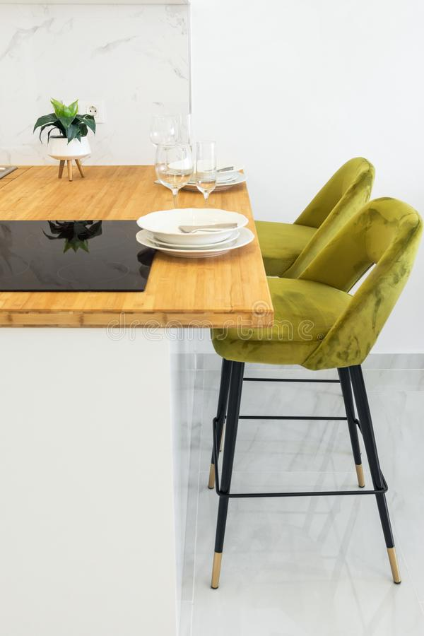 Modern minimalist open kitchen interior with wooden countertop vitroceramic cooking surface table setting with plates glasses. High stools on white wall royalty free stock photos