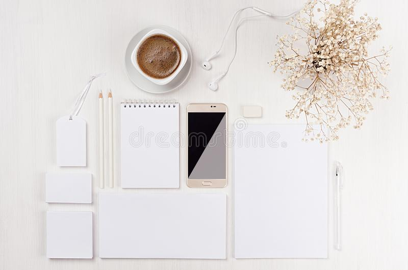 Modern minimalistic elegant feminine work space with white blank stationery, coffee, flowers, phone on white wood board. royalty free stock photos