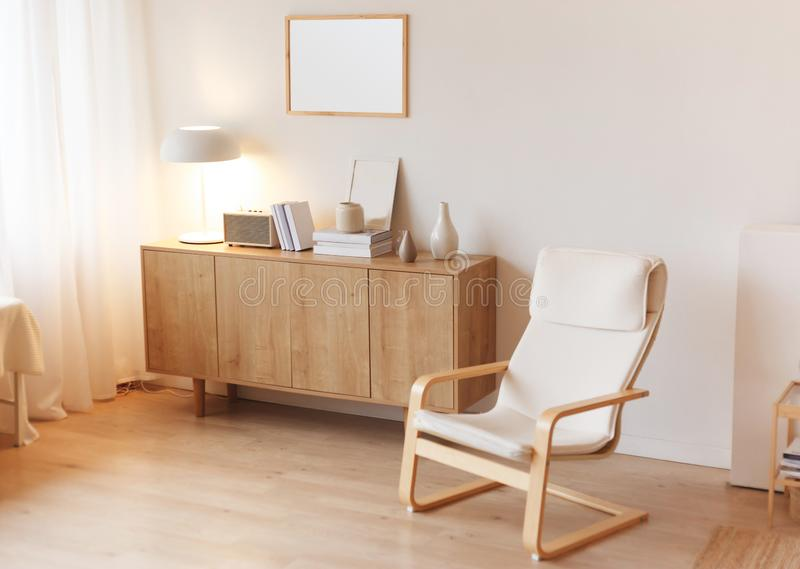 Modern minimalistic interior with chest of drawers an braided armchair. Scandinavian style. stock photo