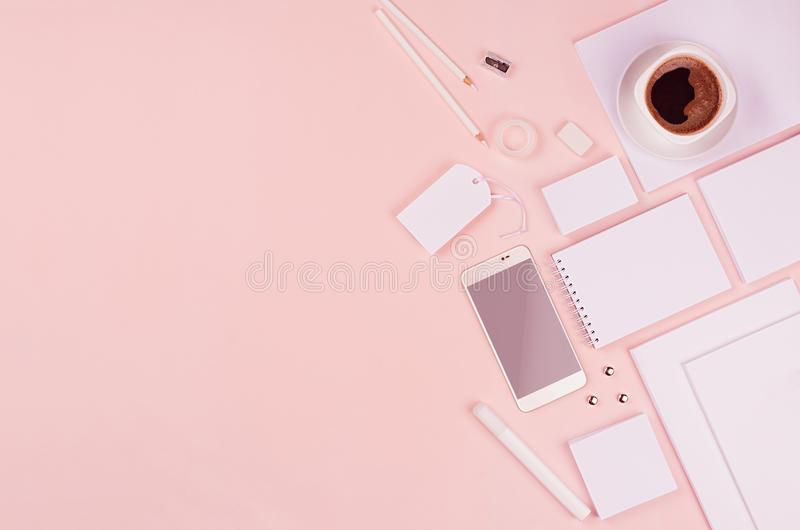 Modern minimalistic spring workspace with white blank stationery, phone, coffee on soft pastel pink background. stock photo