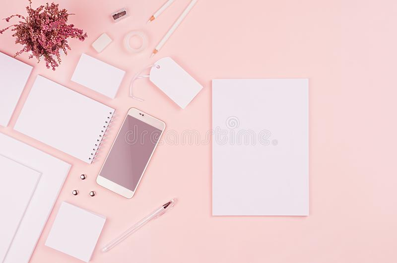 Modern minimalistic spring workspace with white blank stationery on soft pastel pink background, top view, copy space. royalty free stock photo