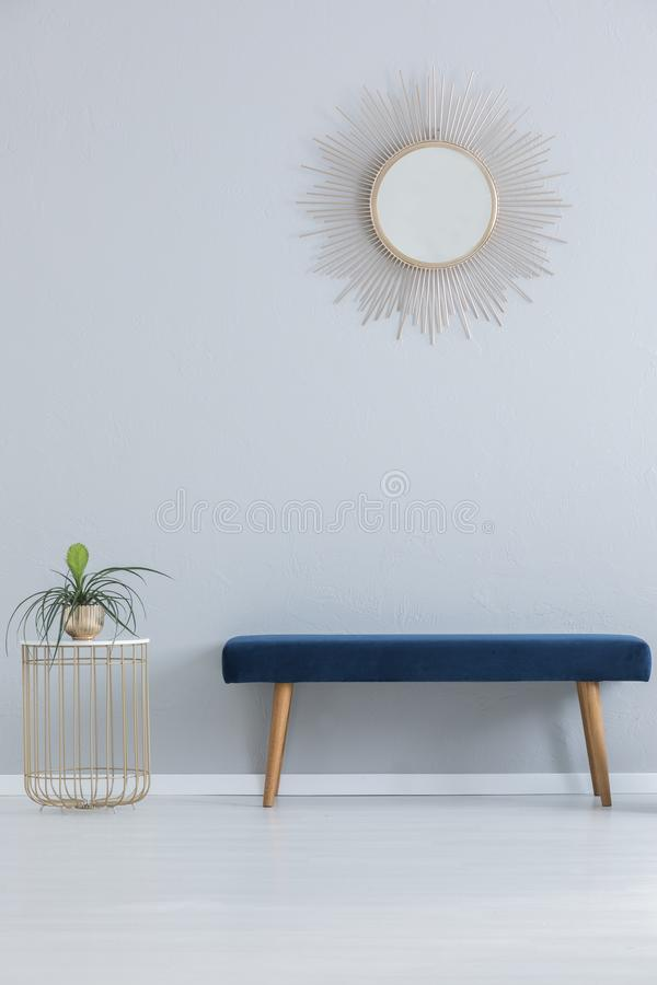 Modern mirror above blue settee and stylish table with plant in golden pot, real photo. With copy space stock photography