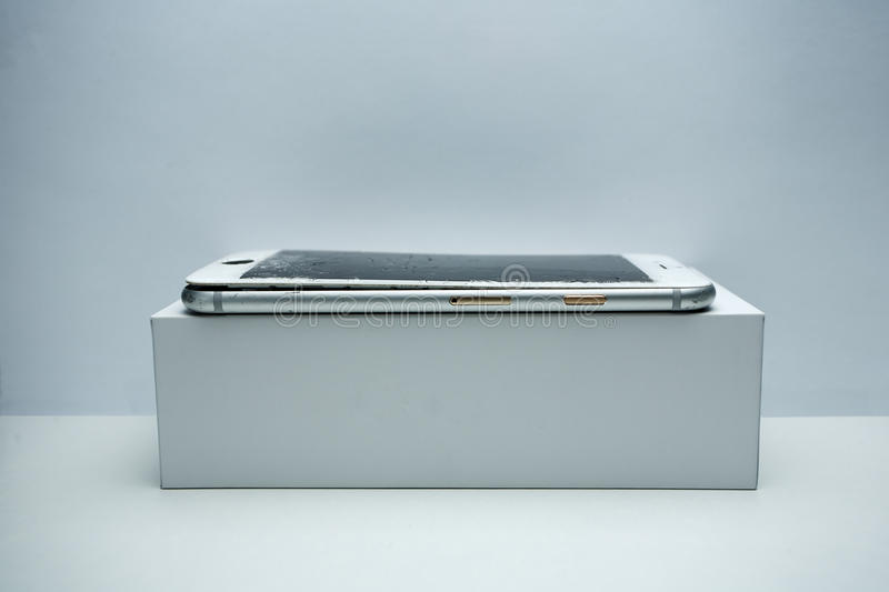 Modern mobile phone with broken screen on white background.  royalty free stock image