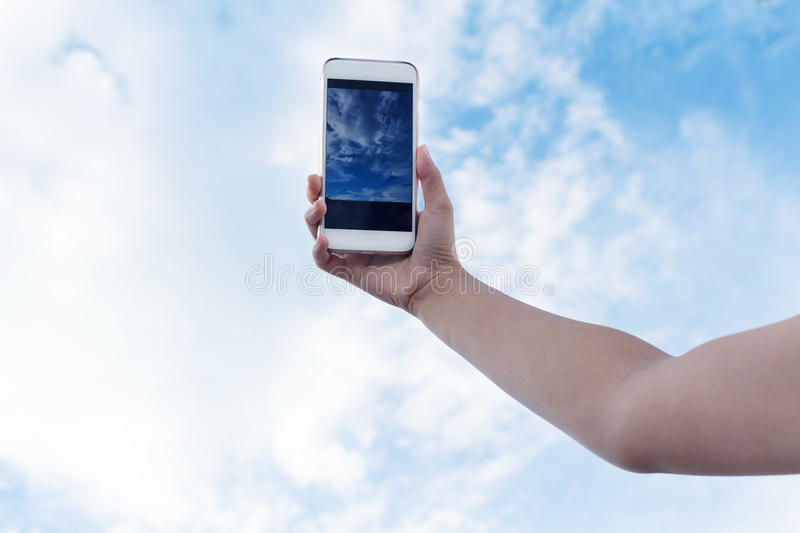 Modern mobile phones against blue sky. Happy people showing their modern mobile phones against blue sky royalty free stock photography