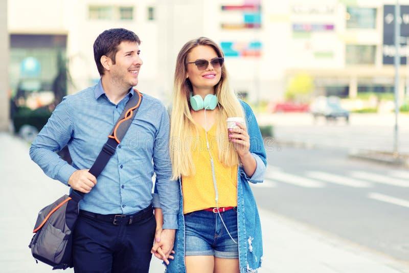 Modern modieus gelukkig paar die samen bij de straatholding van het stadscentrum handen en het glimlachen lopen royalty-vrije stock foto