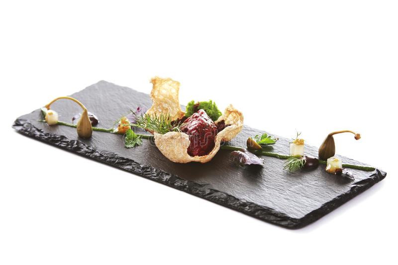Modern Molecular cuisine. Molecular modern cuisine. Chips Pigskin with tartare or carpaccio of beef. Stock image. Isolated on white stock image