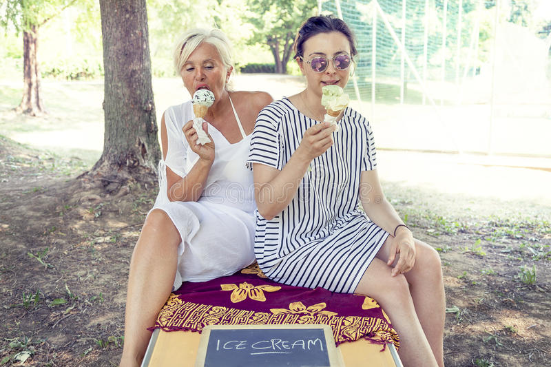 Modern mom and young daughter eating ice cream. Sitting on a deckchair in a water park on summertime. Concept of beautiful people having fun in summertime stock photo