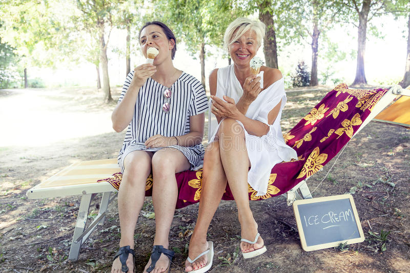 Modern mom and young daughter eating ice cream. Sitting on a deckchair in a water park on summertime. Concept of beautiful people having fun in summertime royalty free stock image