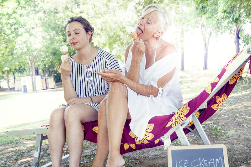 Modern mom and young daughter eating ice cream. Sitting on a deckchair in a water park on summertime. Concept of beautiful people having fun in summertime royalty free stock images
