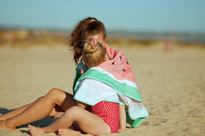 Mother and daughter wrapped in watermelon towel spending time stock images