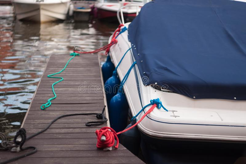 A modern motor boat windshield and bow deck covered in a blue canvas rain cover. stock images
