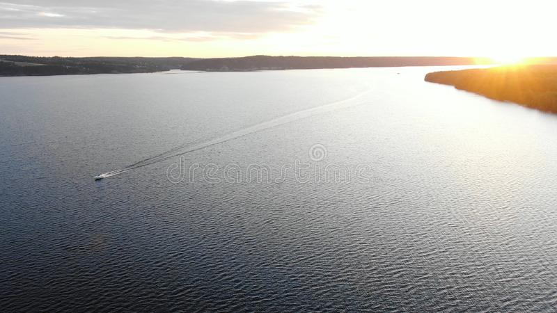 Modern motorboat silhouette sails along wide calm river. Leaving waves against rising sun upper view royalty free stock images
