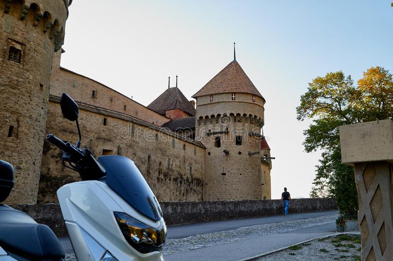 Modern motorcycle in the courtyard of an old stone castle. Modern motorcycle in the courtyard of an ancient stone castle. Summer travel concept royalty free stock image