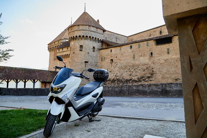 Modern motorcycle in the courtyard of an old stone castle. Modern motorcycle in the courtyard of an ancient stone castle. Summer travel concept stock image