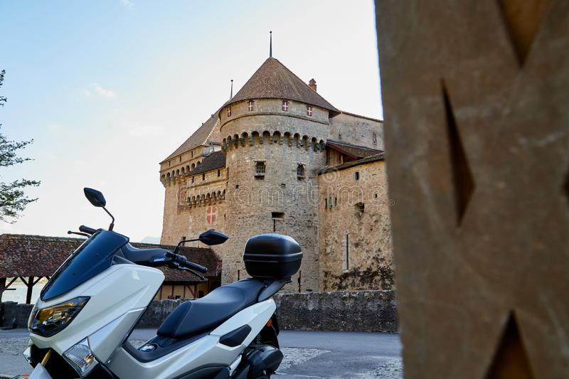 Modern motorcycle in the courtyard of an old stone castle. Modern motorcycle in the courtyard of an ancient stone castle. Summer travel concept stock photography