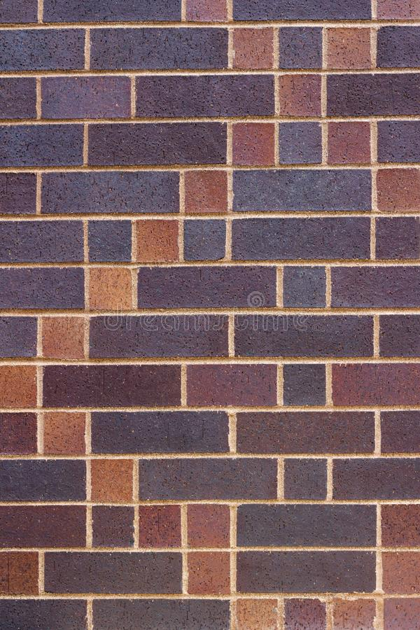 Modern multi-hued brick wall texture in shades of purple and tan stock photo