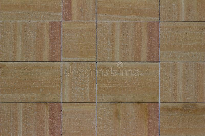 Modern multi-hued stone tile wall texture in shades of beige, tan, and pink. Modern striated and multi-hued stone tile wall texture background in shades of beige stock image