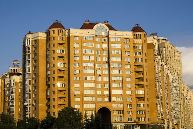 Modern multi-storey orange big house. On background of blue sky royalty free stock image