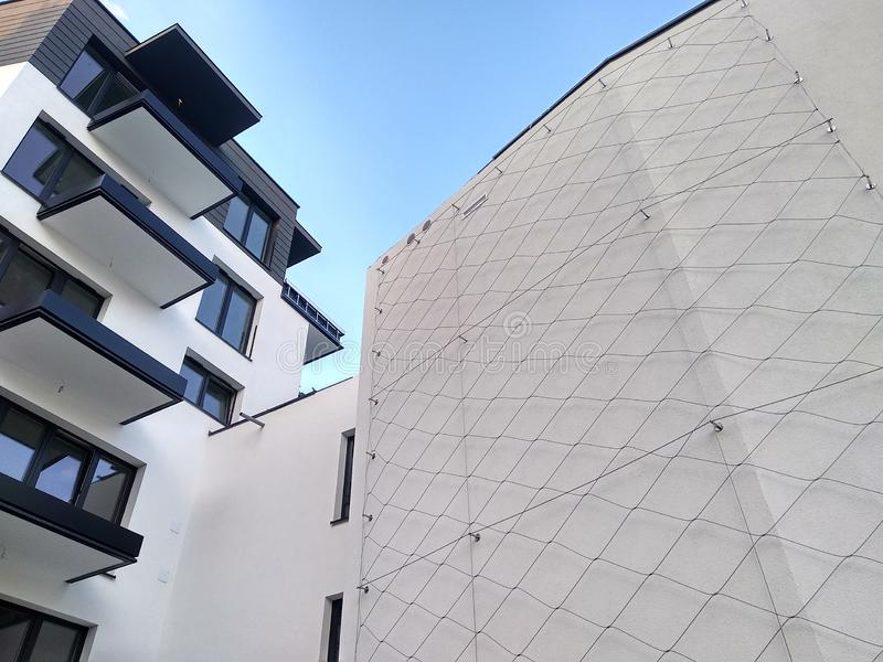 Modern multi-storey residential complex in the city. white concrete wall of the house with Windows and loggias on a Sunny day. Modern multi-storey residential stock photography