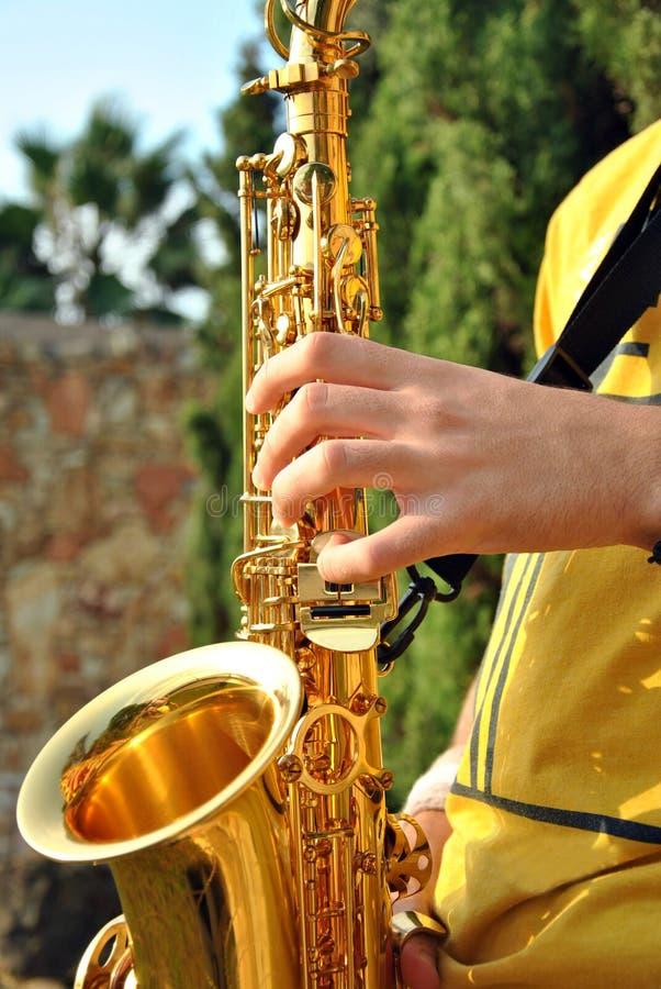 Modern musiker som poserar med hans saxofon royaltyfri bild