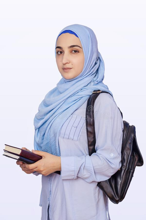 Modern Muslim student girl in hijab. Young middle-eastern college student with backpack holding books and notepads. Isolated on stock photography