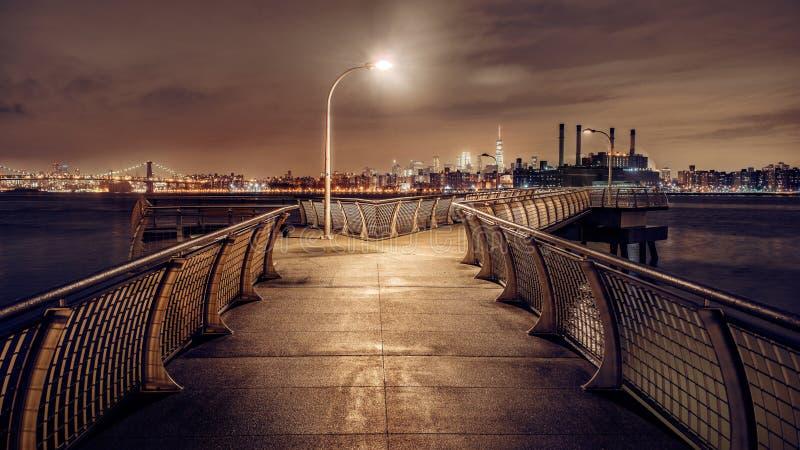 Modern nattpir i Brooklyn med sikt till panorama för New York City horisontManhattan Midtown med skyskrapor royaltyfri foto