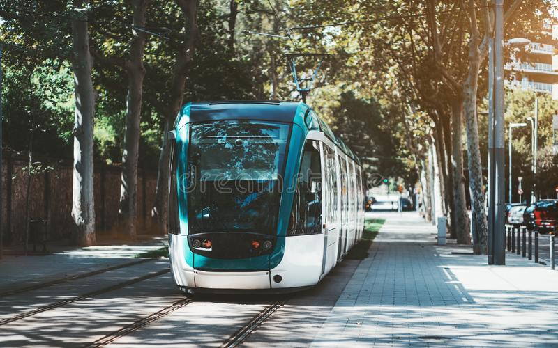 Modern tram in a city alley. A modern neat tram in city alleyway surrounded by trees; blue and white city streetcar near the sidewalk made of pavement stones royalty free stock photo