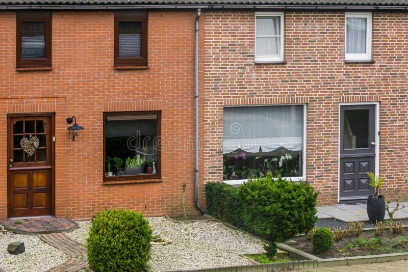 Modern Nederlands terrasvormig huis buiten met tuinen, installaties achter de vensters, huizen in een Nederlands dorp stock afbeelding