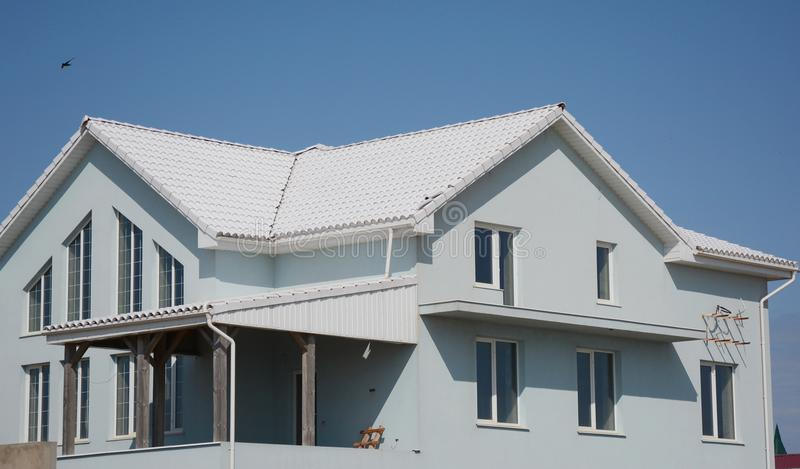Modern house building with white tiled roof. royalty free stock photo
