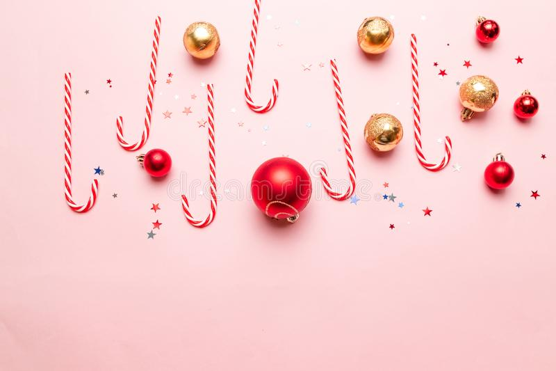 Modern New Year or Christmas banner with striped sweets, gold and red balls, gliter star decor on a pink background. Creative New Year or Christmas banner with stock photos