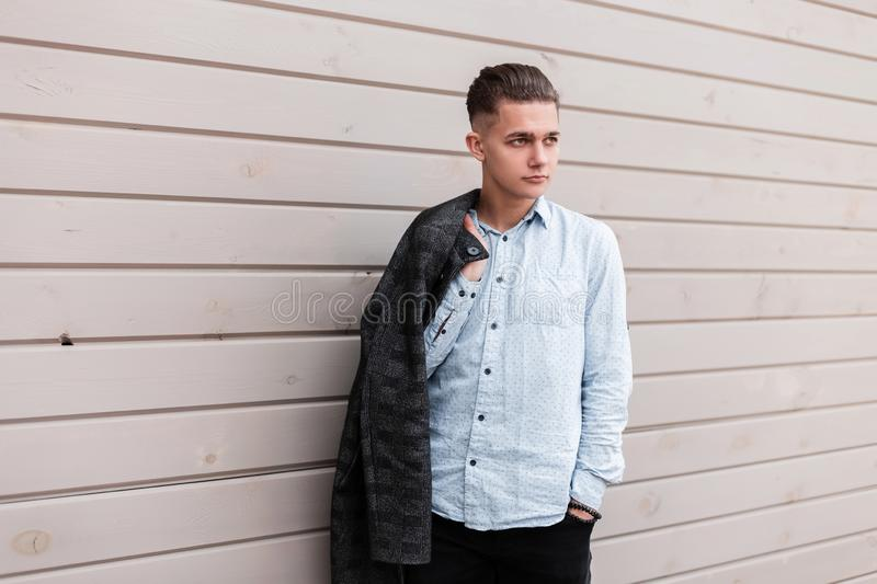 Modern nice young man with a trendy hairstyle in fashionable elegant clothes near a vintage wooden building outdoors. European guy. Model relaxes warm day in royalty free stock photo