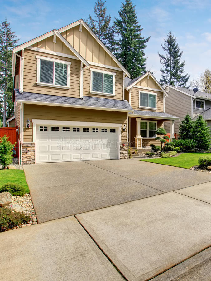 Modern northwest home with tan exterior, and garage. Modern northwest home with tan exterior, garage, and well kept lawn stock image