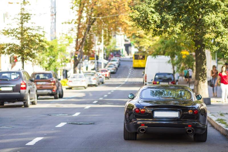 Modern ny bil på sidan av gatan Rader av bilar som parkeras på fotografering för bildbyråer