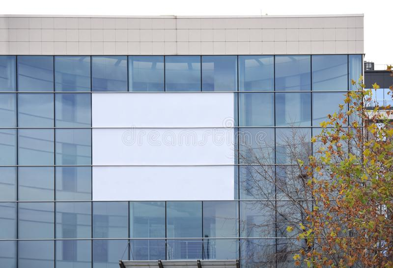 Modern ny glass byggnad med stort vitt utrymme för kommersiell affär arkivbild