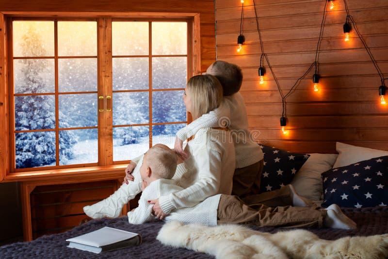 Modern och barn vilar i ett landshus Tillsammans ligger skjuter de på sängen och ut fönstret till snöskogen royaltyfri foto