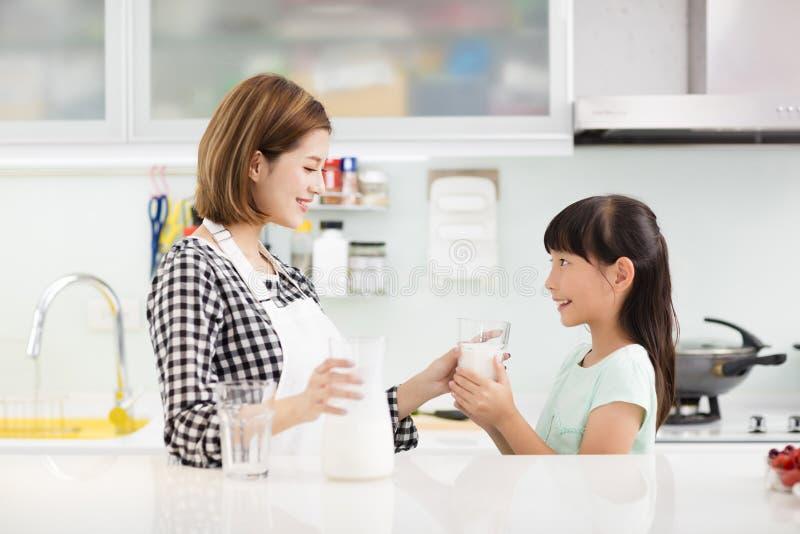 Modern och barnet, i att dricka för kök, mjölkar royaltyfria bilder