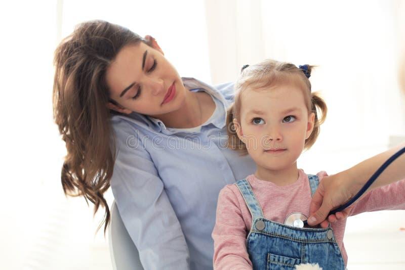 Modern och barnet i doktorskontoret som möter det pediatriskt, sitter de på skrivbordet i sjukhus royaltyfria bilder