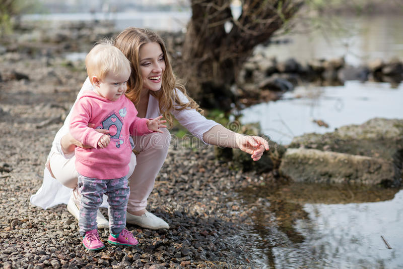 Modern och barnet på banken av floden royaltyfria bilder