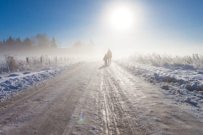 Modern och barnet på dimmig snow brukar vägen royaltyfri fotografi