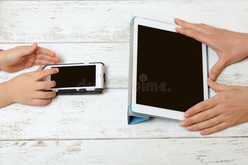 Modern och barnet rymmer minnestavlan och telefonen arkivfoto