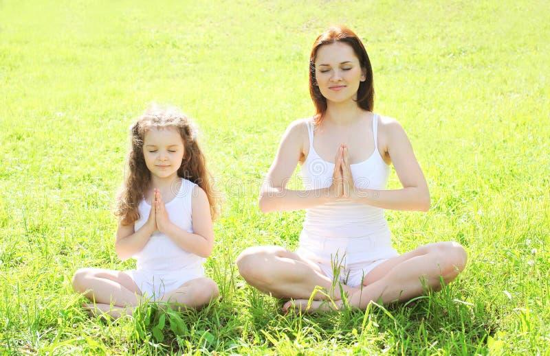 Modern och barnet som gör yoga som in mediterar, poserar lotusblomma royaltyfri fotografi